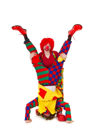 Couple funny full dressed clowns upside down photo