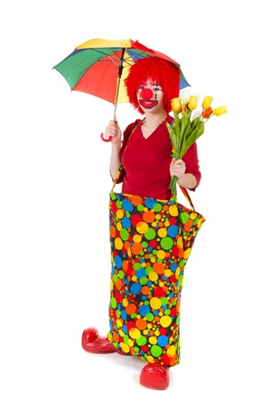 Funny clown with flowers and umbrella in the studio photo