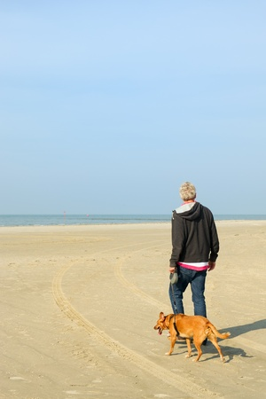 Man walking his dog at the tranquil beach photo