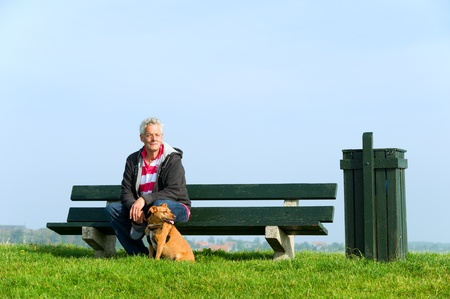 sitting in the bench: Elderly man with his dog at bench outdoor