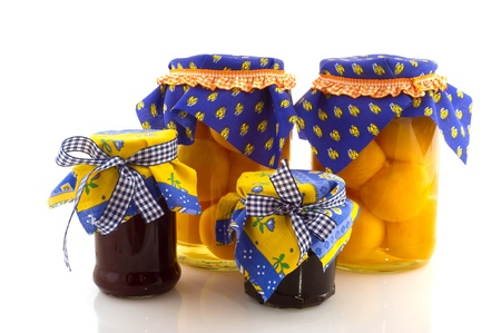 Pots full with preserved fruit als jam and peaches photo