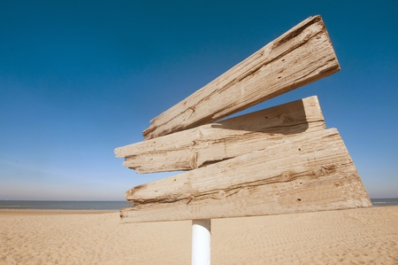Empty wooden direction sign at the tranquil beach photo