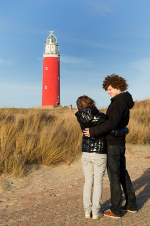 Red lighthouse at the Dutch island Texel with young couple photo