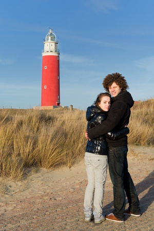 Red lighthouse at the Dutch island Texel with young couple Stock Photo - 9357414