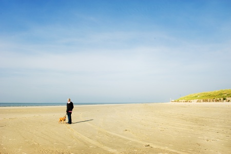 Walking the dog at the lonely beach Stock Photo - 9357423