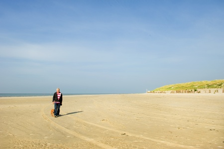 Walking the dog at the lonely beach Stock Photo - 9357418