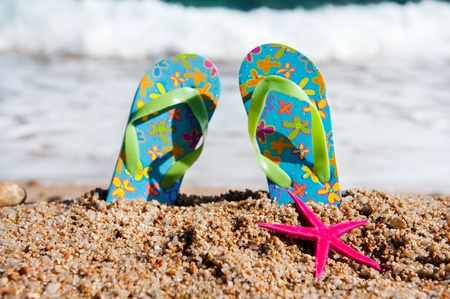Flip flop sandals at the beach near the water line photo