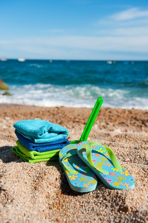 Flip flops and flowers at the beach Stock Photo