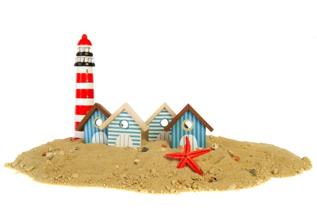 huts: row striped beach huts with lighthouse in the sand Stock Photo