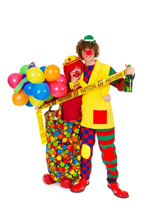 Couple funny full dressed clowns with bottle wine in party zone photo
