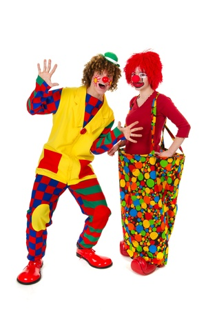 Couple funny full dressed clowns in the studio photo