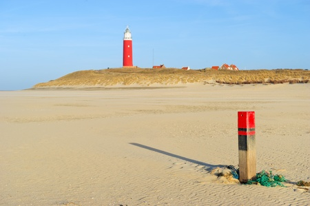 Green old fishing net and pole at the beach with lighthouse Stock Photo - 9514785