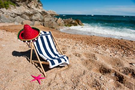 Empty beach chair with striped towel near the sea photo
