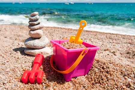 Pile of stacked stones and plastic toys at the beach photo
