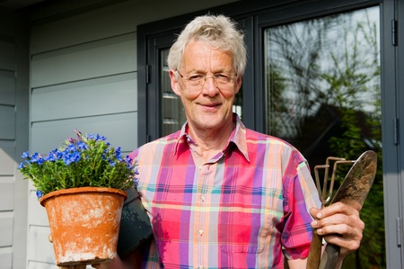 Elderly man is working with plants in the garden photo