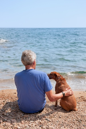 dog rock: Elderly man with his dog at the summer beach