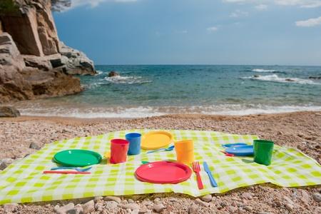 瀬戸物: ビーチでカラフルなプラスチック製食器類でピクニック