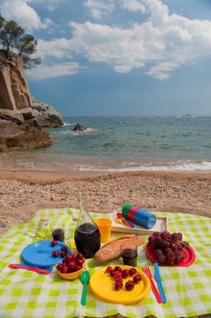 tasty food on colorful plastic crockery at the beach photo