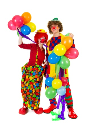 Couple funny full dressed clowns with many balloons photo