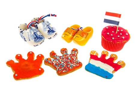 Dutch cookies and wooden clogs on white background photo
