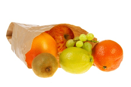 Paper bag with various fresh fruit isolated over white background photo
