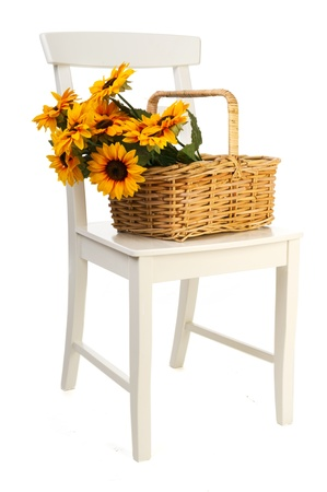 life styles: Romantic still life with a basket sunflowers on a white chair