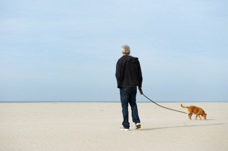 Lonely elderly man with dog at the beach