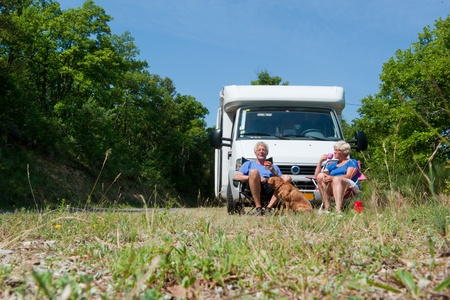 Elderly couple with their dog is travel by camping car photo