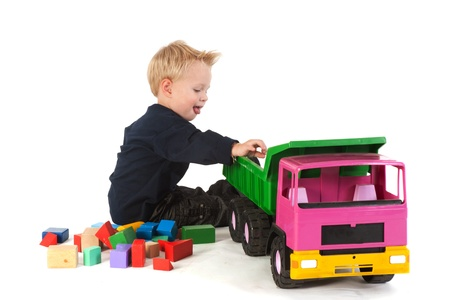 Little blond boy is playing with plastic truck and blocks Stock Photo - 9960002