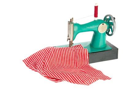 maquina de coser: M�quina de coser verde con ropas rojas aisladas sobre fondo blanco