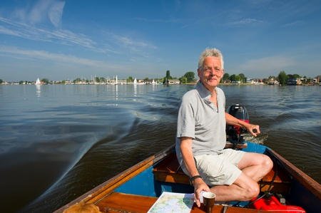 plassen: Elderly man is in motorboat at recreational water in Holland Stock Photo