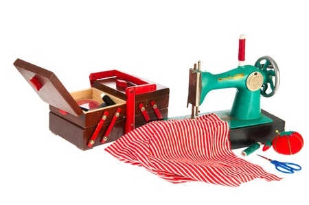 Green sewing machine with red clothes isolated over white background photo