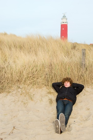 Young man is sleeping at the Dutch beach near the lighthouse photo