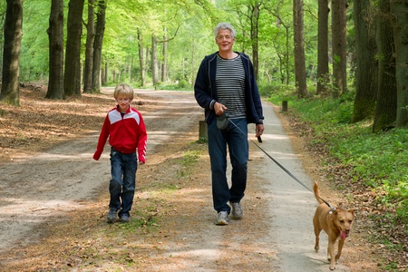 Grandpa and grandchild are walking the dog in the forest photo