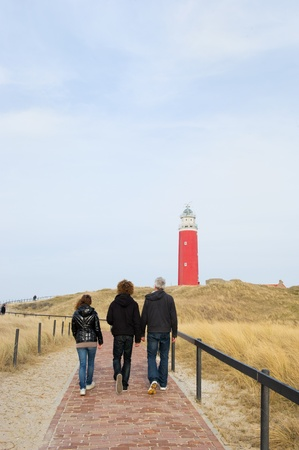 Three persons are walking to the red lighthouse photo