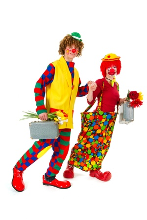 Funny clowns couple is traveling with suitcases and flowers photo