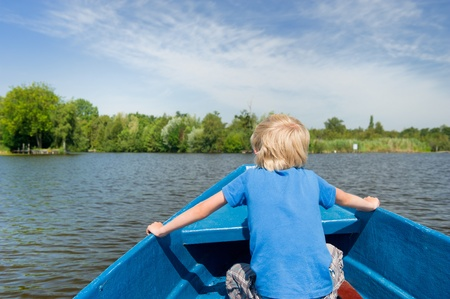 plassen: Blonde boy in blue boat on the water