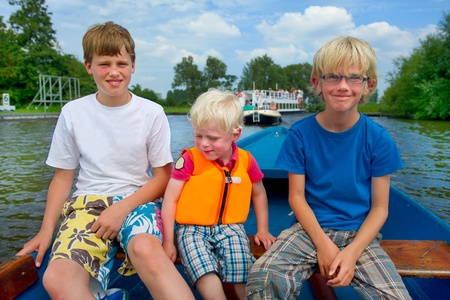 plassen: Three blonde boys in a boat on the water Stock Photo