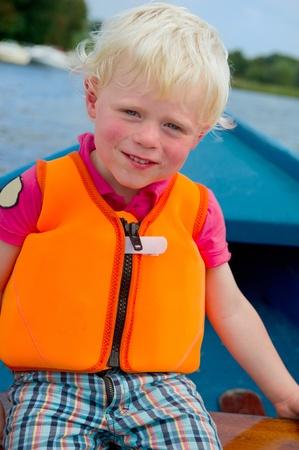 plassen: Little blond boy in life jacket on the boat