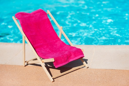 beach towel: Beach chair with towel near the swimming pool Stock Photo
