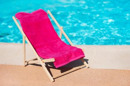 towel: Tumbona con una toalla cerca de la piscina