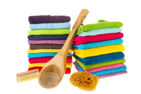Stacked colorful towels and wooden sauna equipment photo