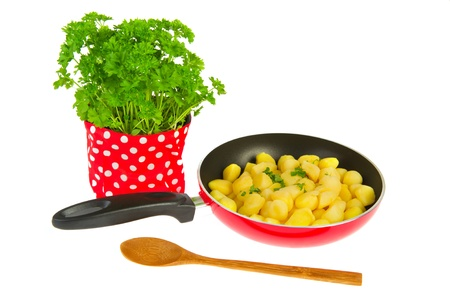 Frying new potatoes in red pan with fresh parsley photo