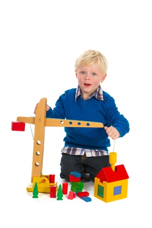 Young blond child is playing with crane and blocks photo