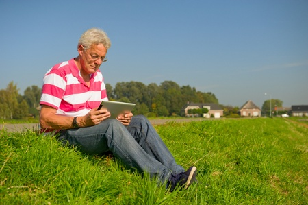 Senior outdoor in nature landscape with tablet PC photo