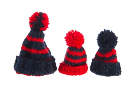 Winter bonnets knitted in blue and red isolated over white background photo