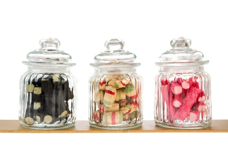 Three filled glass candy jars isolated over white background photo