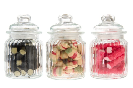 Three filled glass candy jars isolated over white background