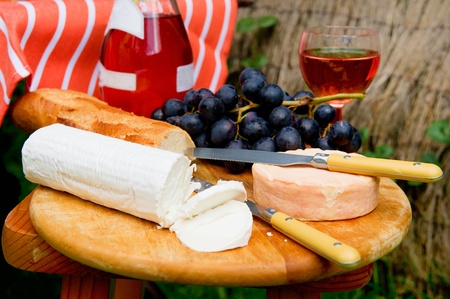 Cheese board outdoor with cheese bread and wine photo