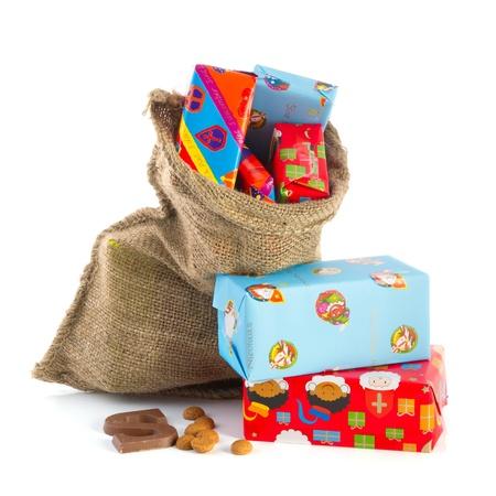 sinterklaas: Jute-Tasche voller niederl�ndischen Sinterklaas pr�sentiert mit vielen verpackte Geschenke Lizenzfreie Bilder